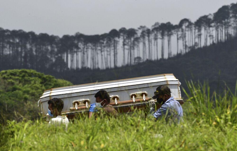 Parentes carregam caixão de vítima da pandemia no cemitério em Honduras