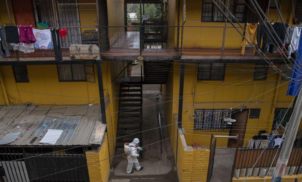 Funcionário da Prefeitura de Santiago, no Chile, executa desinfecção em residências de classe baixa na cidade