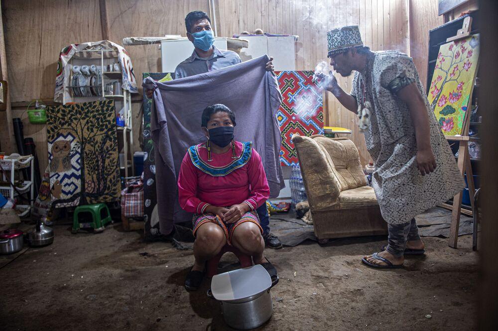Mulher recebe banho de fumaça de ervas medicinais durante ritual de cura na comunidade Cantagallo, onde 300 famílias do grupo étnico Shipibo Conibo vivem em Lima
