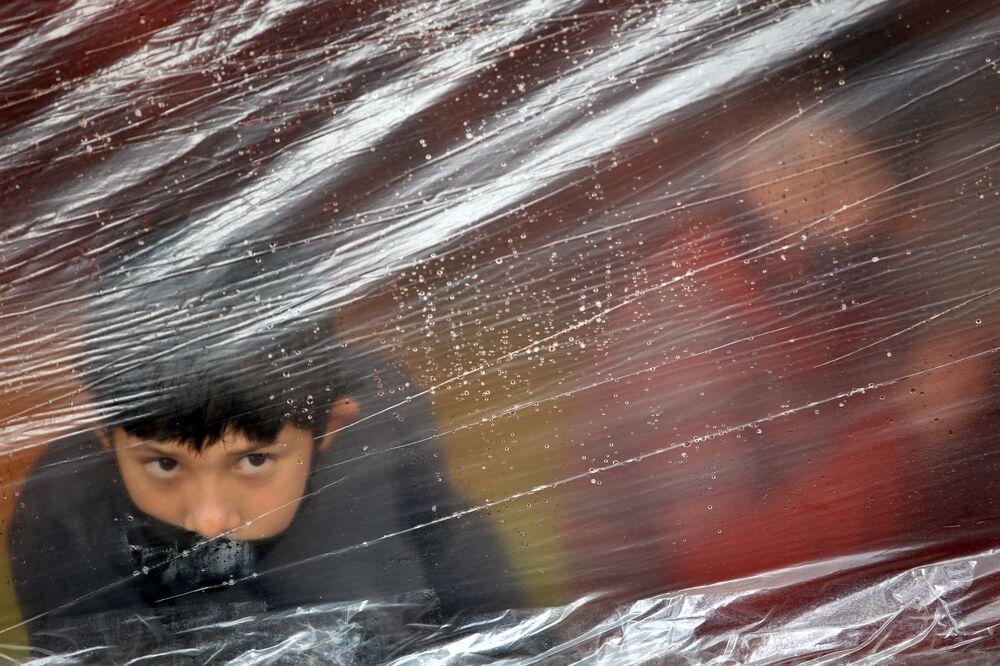Menino olha por protetor de plástico em campo de imigrantes venezuelanos desabrigados e sem trabalho durante a pandemia da COVID-19 em Bogotá, Colômbia