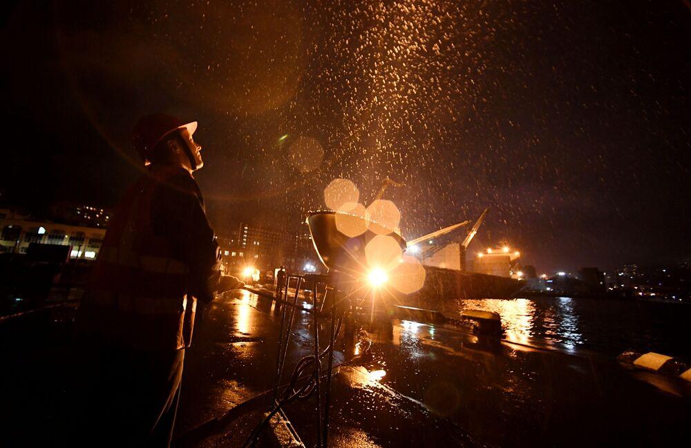 Trabalhadores iluminam o céu com holofotes no terceiro píer do porto de Vladivostok durante celebração do Dia da Vitória