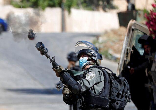 Soldado israelense atira gás lacrimogênio em manifestantes que protestavam contra a demolição de uma casa palestina na Cisjordânia ocupada, 24 de junho de 2020