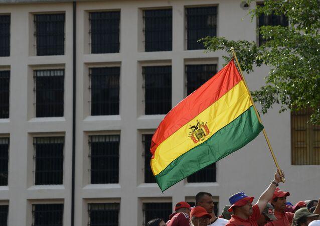 Um apoiador pró-governamental agita uma bandeira nacional boliviana durante um comício em Caracas, Venezuela, 16 de novembro de 2019