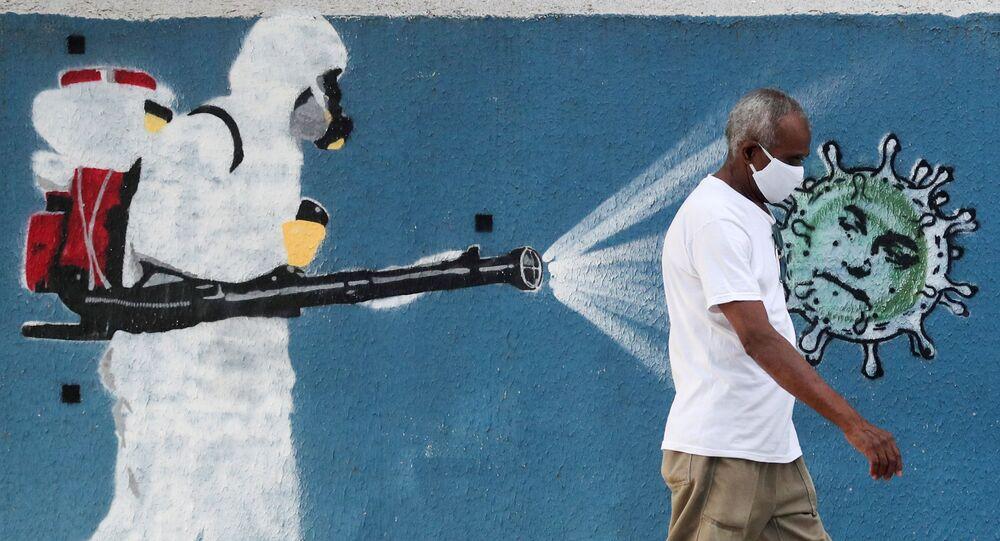 Homem caminha em frente a grafite retratando profissional de limpeza de máscara espalhando coronavírus