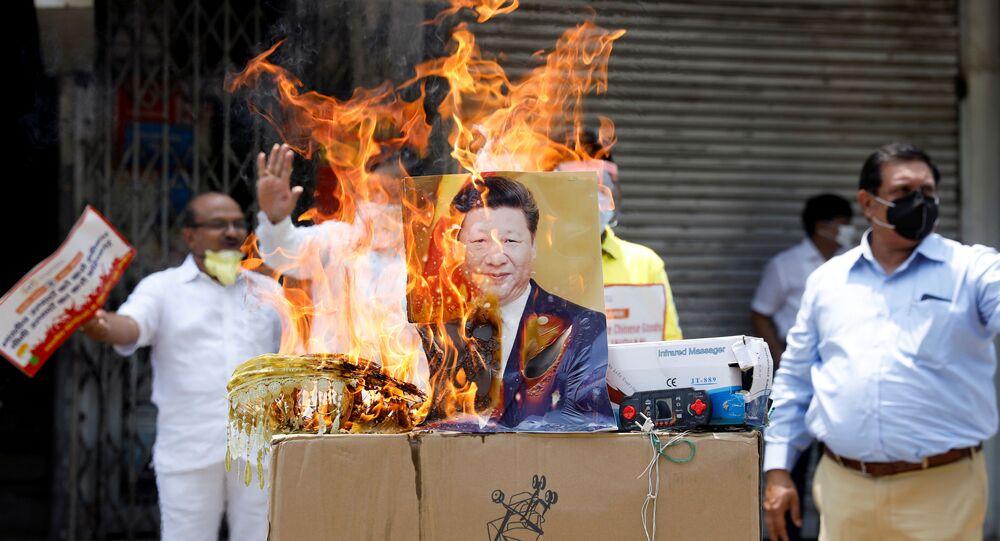 Manifestantes queimam produtos fabricados na China e um pôster do presidente chinês Xi Jinping durante protesto contra a China, em Nova Deli, na Índia, em 22 de junho de 2020