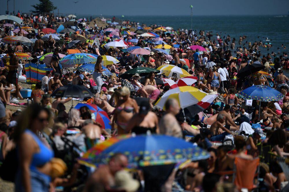 Banhistas se bronzeiam em praia no sul do Reino Unido