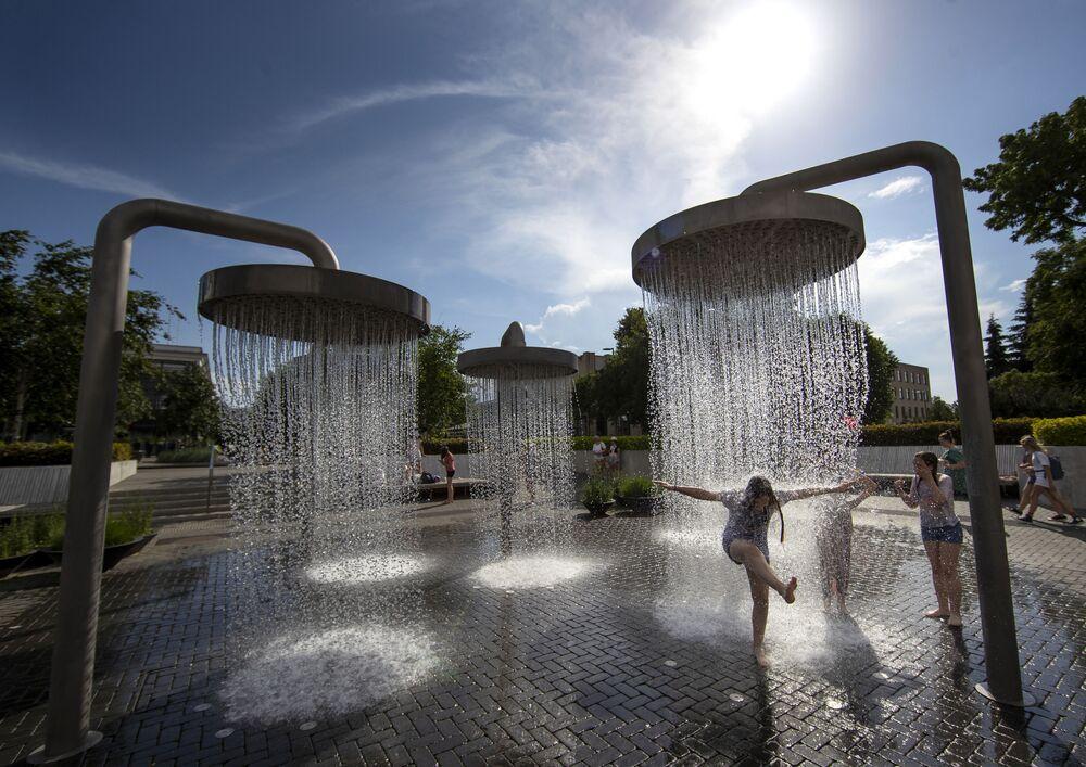 Crianças brincam em fonte pública na capital da Lituânia conforme a cidade passa por uma onda de calor