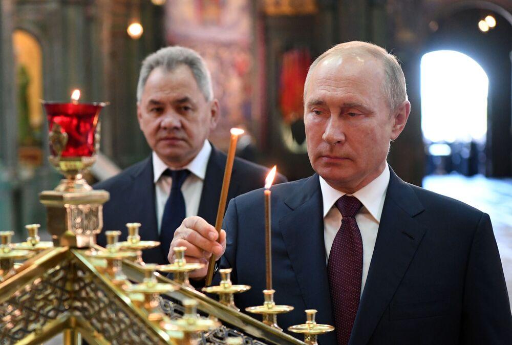 Presidente russo Vladimir Putin e ministro da Defesa Sergei Shoigu acendem velas na Igreja das Forças Armadas, inaugurada em 22 de junho