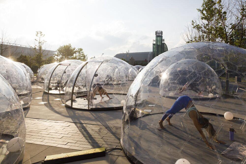 Pessoas realizam exercícios físicos, em bolhas transparentes, respeitando as medidas de distanciamento no combate ao coronavírus, em Toronto, Canadá