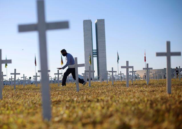 Em Brasília, um ativista caminha em frente a cruzes que simbolizam os mortos pela COVID-19. O protesto contra o presidente brasileiro, Jair Bolsonaro, aconteceu em 28 de junho de 2020, em frente ao Congresso Nacional.