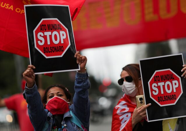 Manifestantes seguram cartazes, com a inscrição Ato Mundial, Stop Bolsonaro, durante protesto contra o presidente Jair Bolsonaro e em apoio à democracia, em São Paulo, Brasil, 28 de junho de 2020