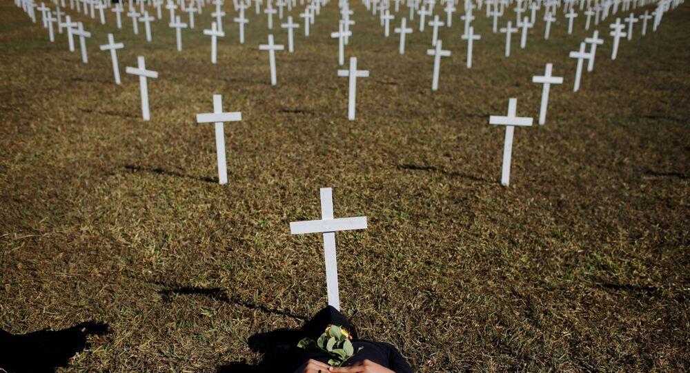 Ativista ao lado de cruzes, simbolizando os que morreram por coronavírus, em frente ao Congresso Nacional durante protesto contra presidente do Brasil, Jair Bolsonaro, em Brasília, Brasil, 28 de junho de 2020