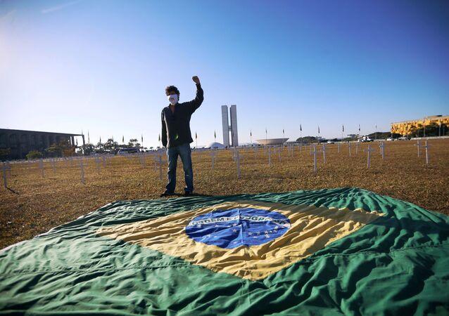 Ativista ao lado da bandeira brasileira e de cruzes simbolizando os que morreram por COVID-19, em frente ao Congresso Nacional, Brasília, Brasil, 28 de junho de 2020