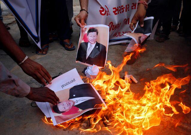 Manifestantes queimam cartazes do presidente chinês Xi Jinping durante um protesto contra a China, em Ahmedabad, Índia, 16 de junho de 2020
