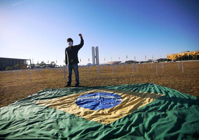 Ativista em frente à bandeira brasileira com cruzes no fundo que simbolizam vítimas da COVID-19 durante protesto contra Bolsonaro em Brasília, 28 de junho de 2020