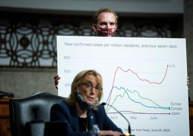 Assessor segura tabela de estatísticas enquanto a senadora norte-americana Maggie Hassan fala sobre os esforços dos EUA para voltar ao trabalho e à escola durante a pandemia, em Washington, EUA, 30 de junho de 2020