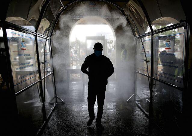 Homem passa por túnel desinfetante antes de entrar em estação de trem no Quênia