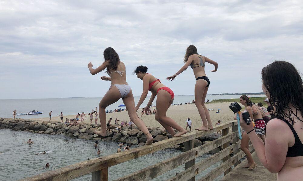 Garotas saltam de uma ponte no lago Sengekontacket nos Estados Unidos
