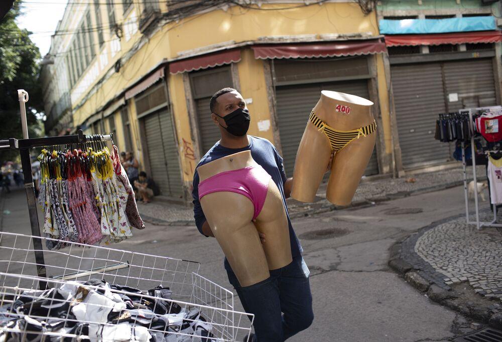 Vendedor com máscara protetora leva manequins no mercado de rua no Rio de Janeiro