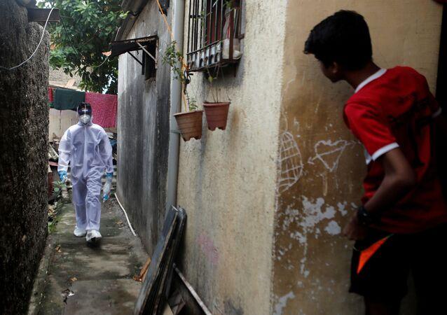 Profissional da saúde usando equipamento de proteção individual contra a doença do coronavírus (COVID-19) caminha por favela de Mumbai, Índia, 27 de junho de 2020.
