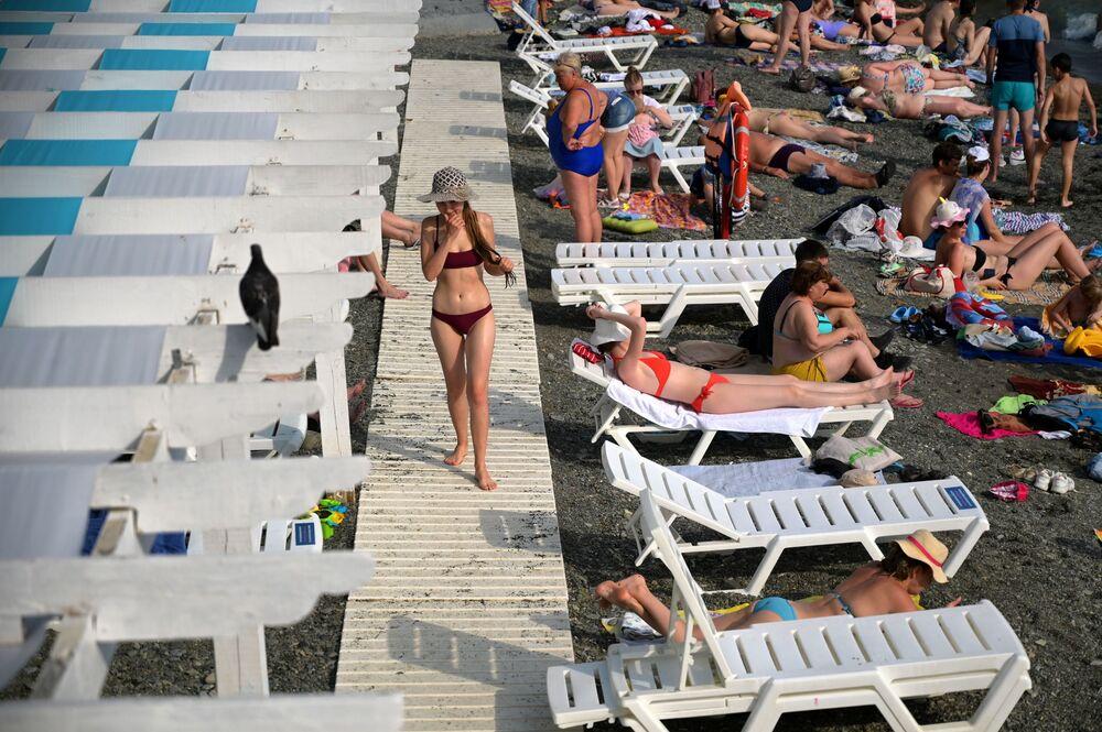 Banhistas descansando em uma praia na cidade de Sochi, na Rússia