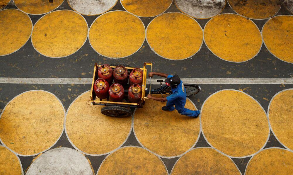 Homem empurra um carrinho com botijas de gás de petróleo liquefeito em Mumbai, Índia