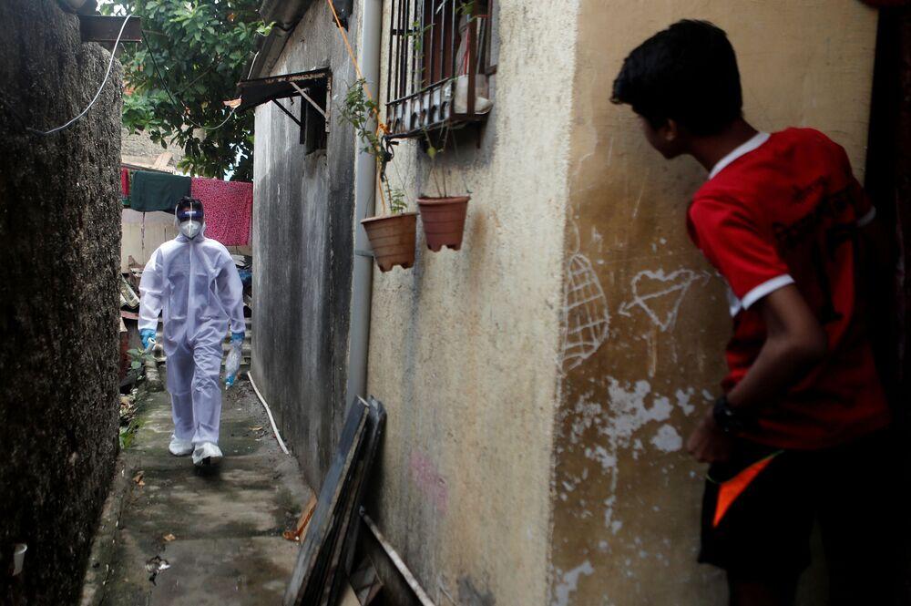Profissional da saúde com traje de proteção individual passa por favela em Mumbai, Índia