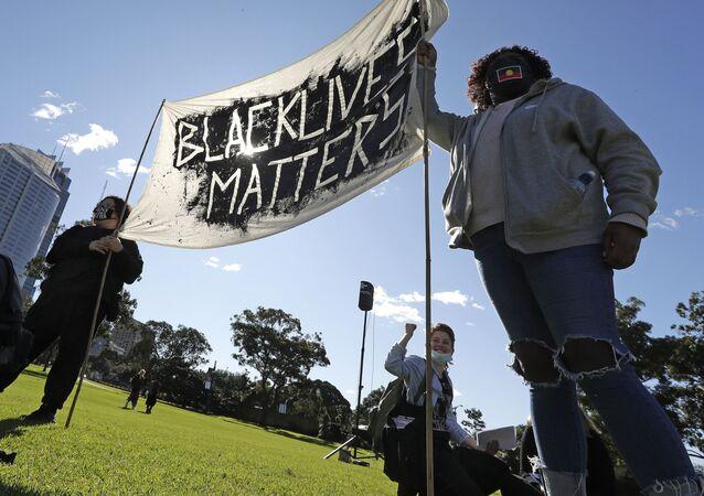 Casal segura faixa com slogan em uma manifestação de apoio aos movimentos Black Lives Matter e Black Deaths in Custody em Sydney, Austrália, 5 de julho de 2020