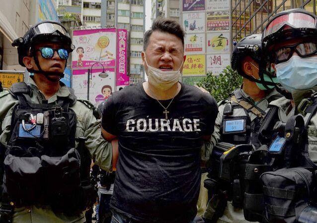 Policiais prendem manifestante atingido com gás de pimenta em Hong Kong