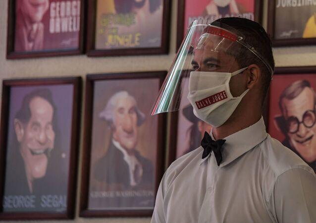 Garçom com máscara e protetor facial no primeiro dia de reabertura de bares e restaurantes, na Vila Madalena, em São Paulo, 6 de julho de 2020