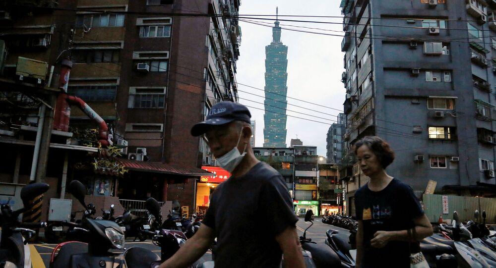 Pessoas usando máscaras para se protegerem da doença COVID-19 enquanto caminham perto do arranha-céu Taipei 101, em Taipé, Taiwan, 7 de julho de 2020