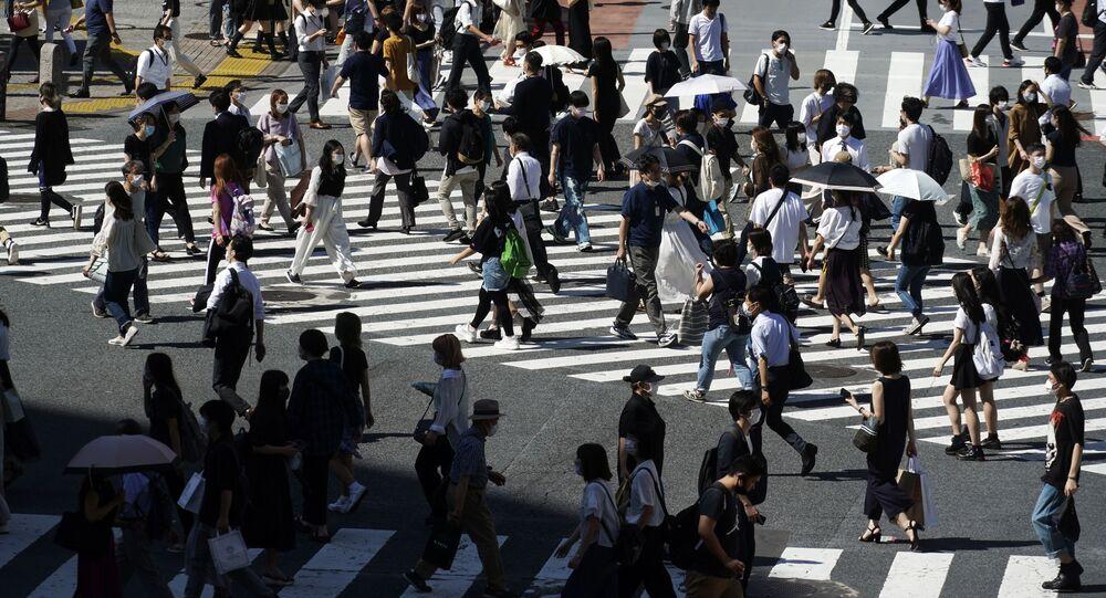 Pessoas usando máscaras faciais protetoras para ajudar a conter a propagação do coronavírus na passagem de pedestres de Shibuya em Tóquio, 2 de julho de 2020