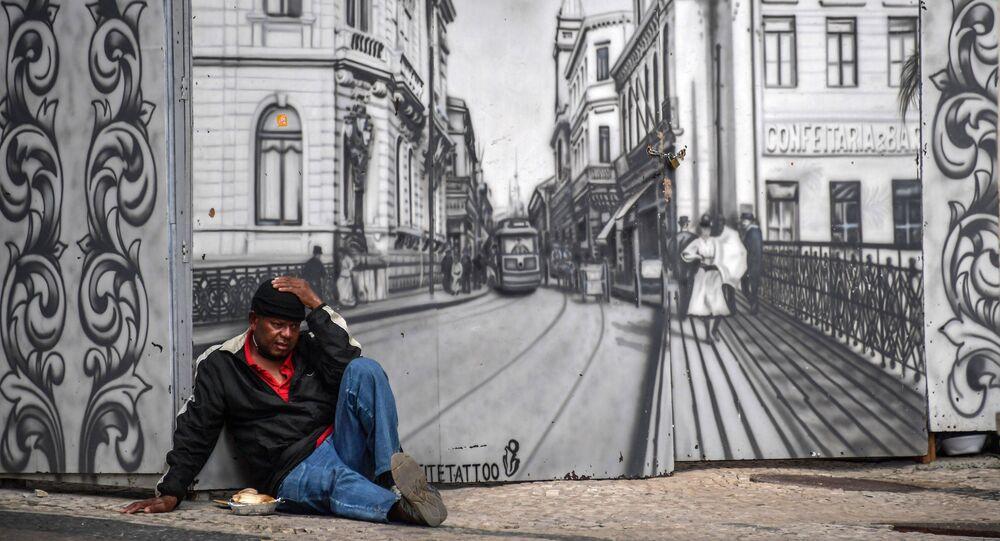 Sem-teto senta na frente de mural representando o centro antigo, em São Paulo, 6 de julho de 2020