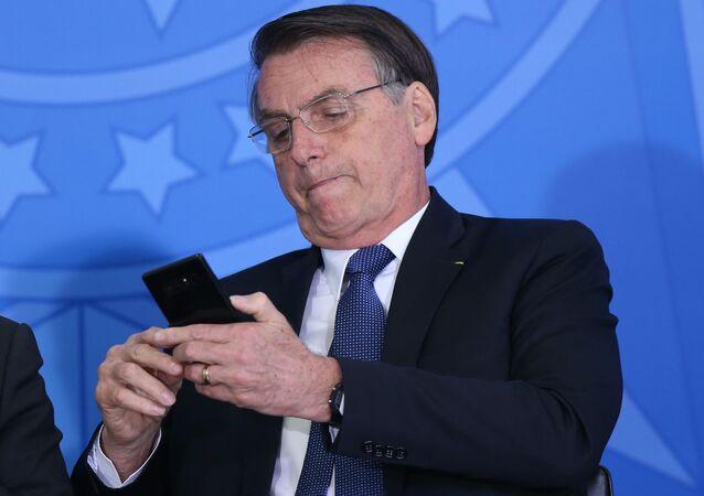 Presidente Jair Bolsonaro mexe no celular durante solenidade no Palácio do Planalto
