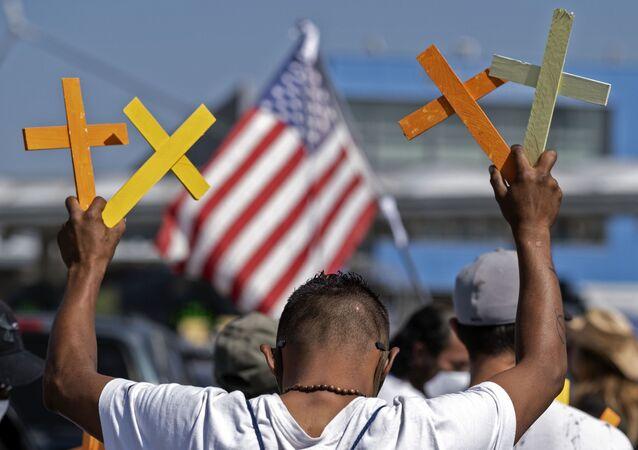 Imigrante deportado dos EUA segura cruzes na cidade mexicana de Tijuana, na fronteira entre EUA e México, 8 de julho de 2020