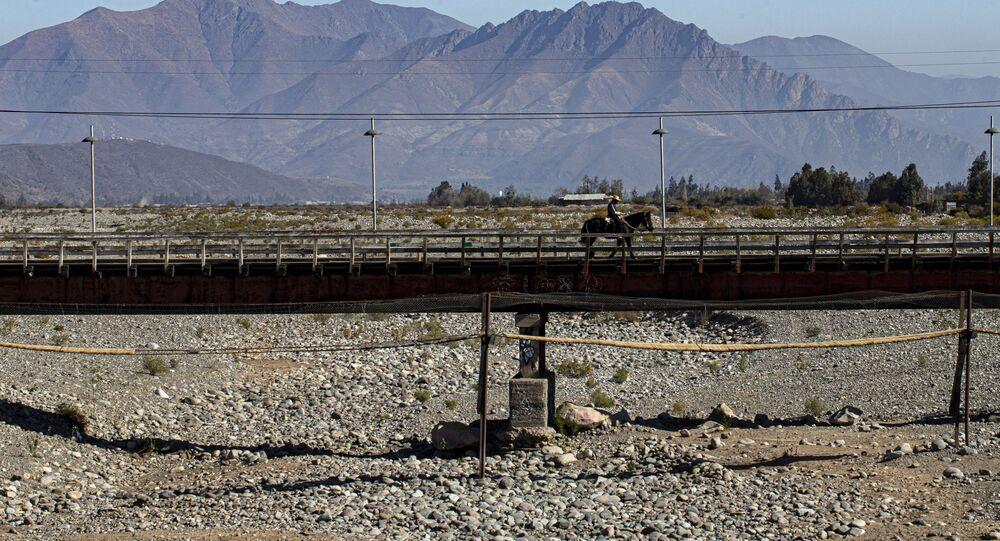 Homem a cavalo cruza uma ponte sobre o leito de um rio que secou devido à pior seca do Chile em mais de meio século, em Putaendo, 23 de setembro de 2019