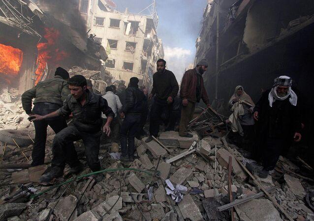 Pessoas andam sobre escombros enquanto outros tentam apagar um incêndio, Damasco, Síria, 9 de fevereiro de 2015