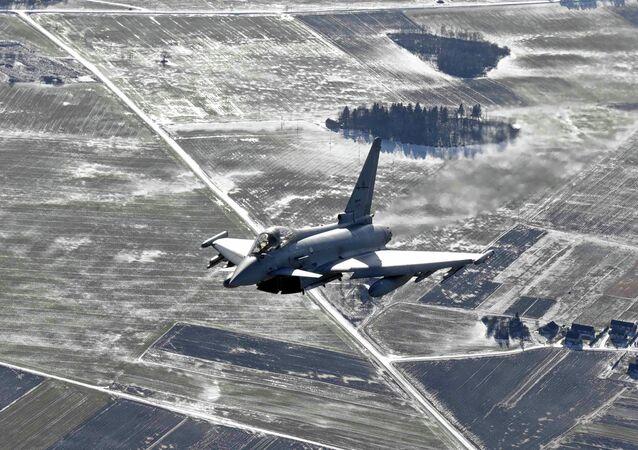 Avião militar italiano do Eurofighter Typhoon patrulha sobre os Bálticos durante uma missão da vigilância aérea da OTAN a partir da base aérea de Zokniai, perto de Siauliai