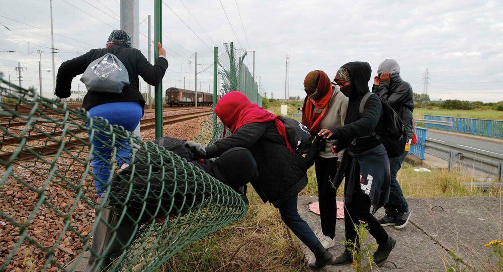 Imigrantes tentando abrir caminho através de cerca junto à linha férrea perto de Calais, na França (29 de julho de 2015).