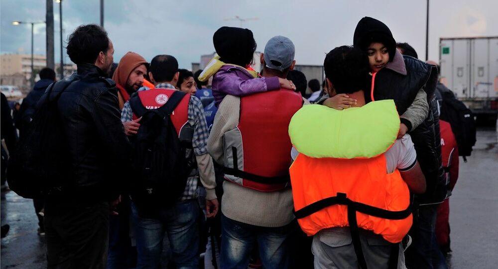 Imigrantes temporariamente detidos caminham no porto da ilha grega de Kos