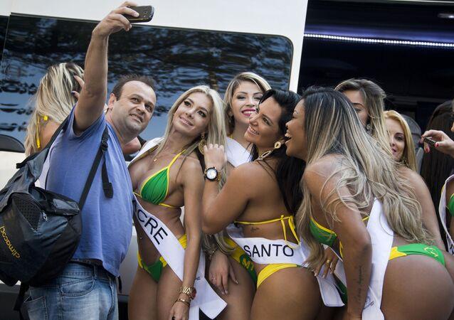 Um homem tira selfie com participantes do concurso Miss Bumbum Brazil 2015 em São Paulo