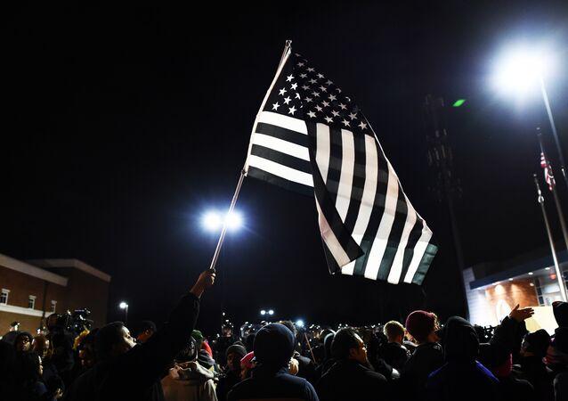 Manifestantes protestam contra a desigualdade racial com bandeira simbólica dos EUA a preto e branco