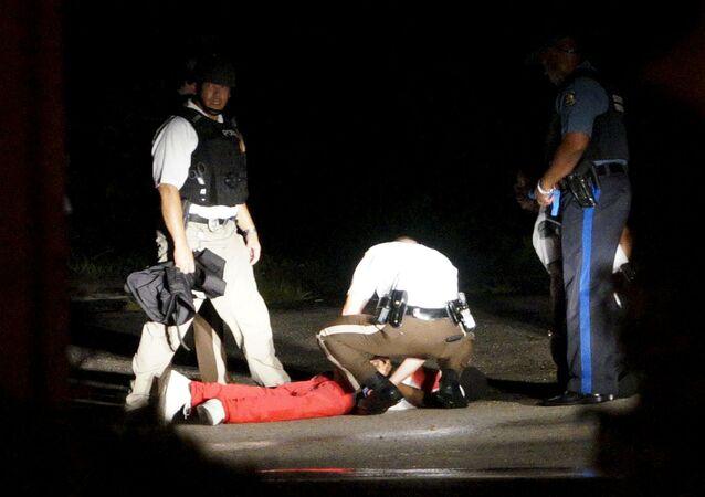 Um manifestante ensanguentado é socorrido por um policial em Fergusson.