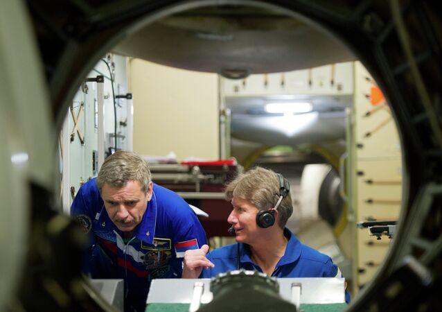 Cosmonautas russos Mikhail Kornienko (E) e Gennady Padalka trabalhando com o simulador