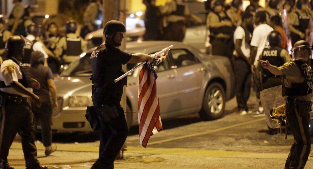 Policial com uma bandeira estadunidense que ele tomou de um manifestante durante os protestos em Ferguson, Missouri