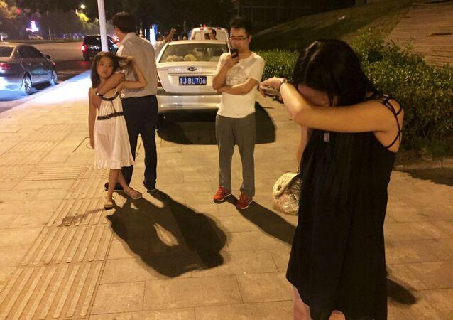 Pessoas nas ruas de Tianjin instantes após a grande explosão que sacudiu a quarta maior cidade da China nesta quarta-feira, 12 de agosto