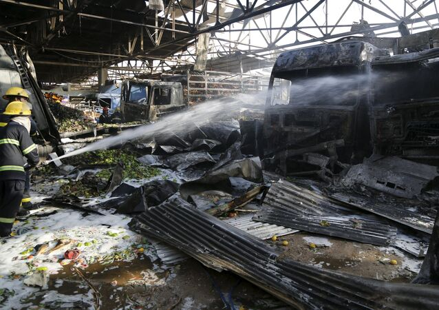 Firemen hose down a burnt vehicle at the site of a truck bomb attack at a crowded market in Baghdad, August 13,2015