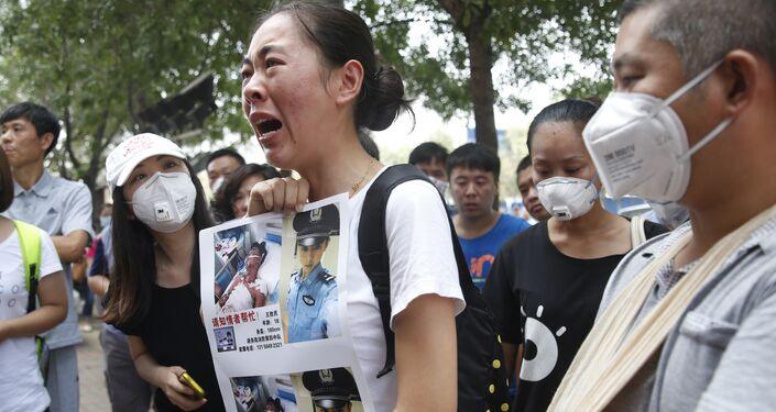 Um membro da família de um bombeiro que desapareceu após as fortíssimas explosões na zona portuária de Tianjin