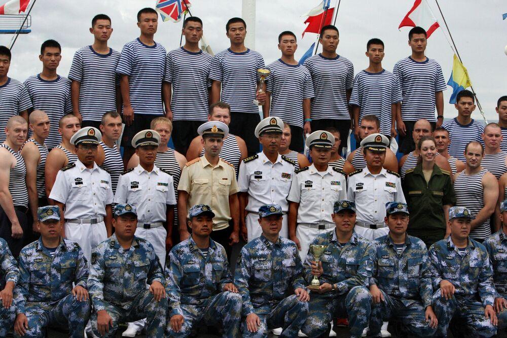 As equipes também irão treinar as ações de defesa aérea. Equipes russa e chinesa tiram uma foto em Vladivostok.