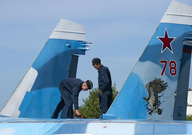 Militares russos preparam o avião Su-33 para o voo de treinamento no polígono dos sistemas de decolagem e aterrissagem Nitka em Crimeia (Rússia).